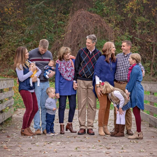Extended family interacting on a wooden bridge during fall