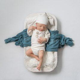 newborn boy wearing sleepy cap laying on white dough bowl