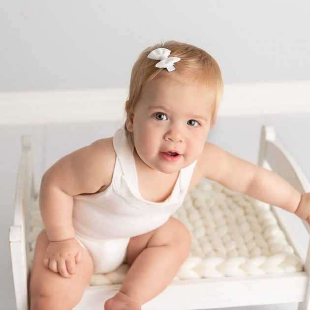 baby girl sitting on a white doll bed in a white studio