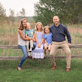 Family of 5 sitting on a wooden fence in front of a tall grass field