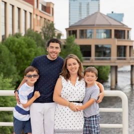 Family of 4 standing on the Blue Bridge in Grand Rapids in front of the Public Museum