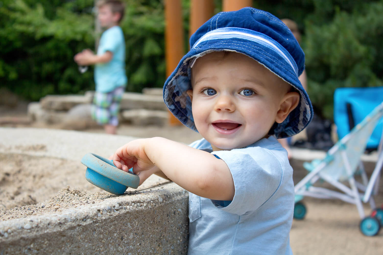 baby boy in blue fisherman hat digging in the sand at Frederik Meijer Gardens
