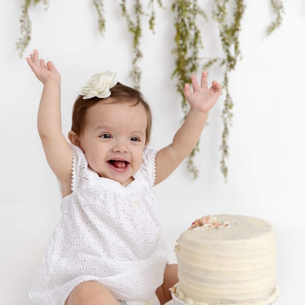 baby girl wearing white dress smiling with arms in the air eating a smash cake