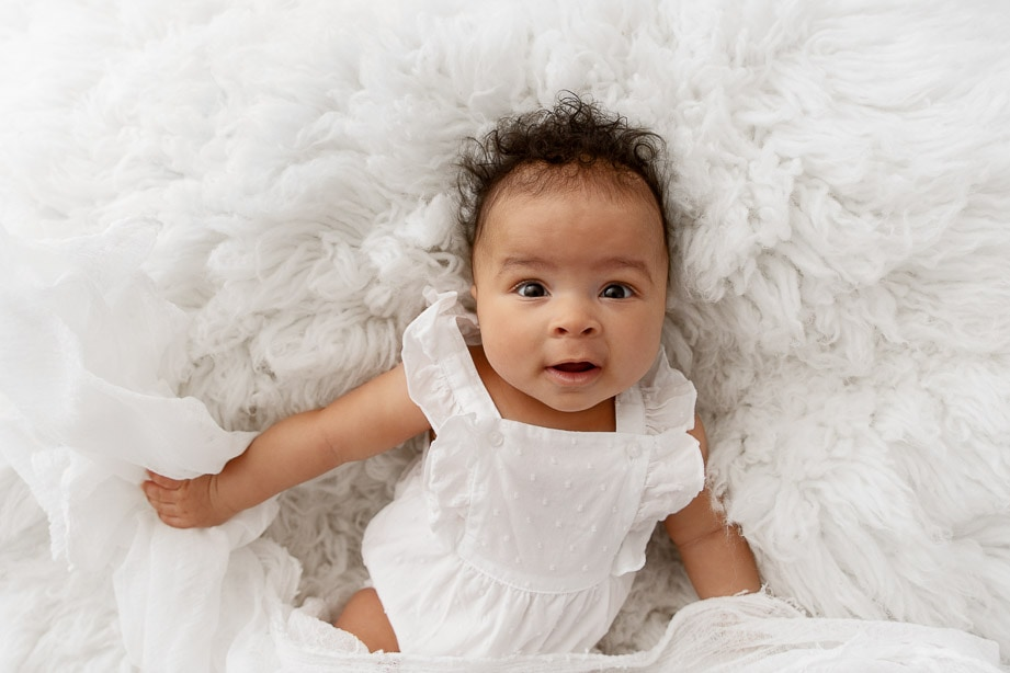3 month baby girl wearing a white romper laying on a white fur looking up at camera