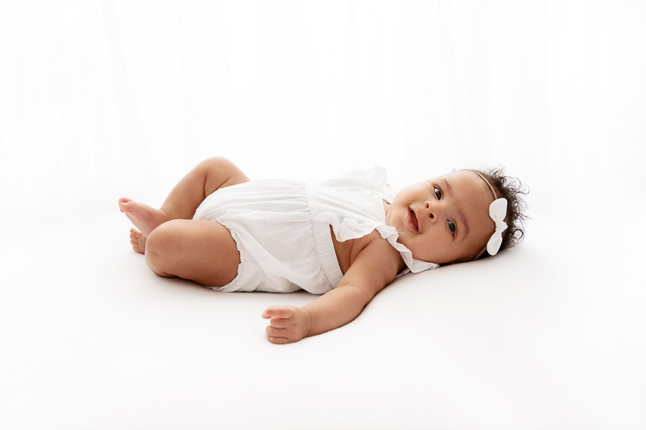 Backlit 3 month baby girl wearing a white romper laying on back in front of white sheer curtains