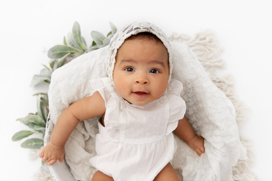 3 month baby girl wearing a white romper and bonnet sitting in a white bowl surrounded by macrame and green leaf stems