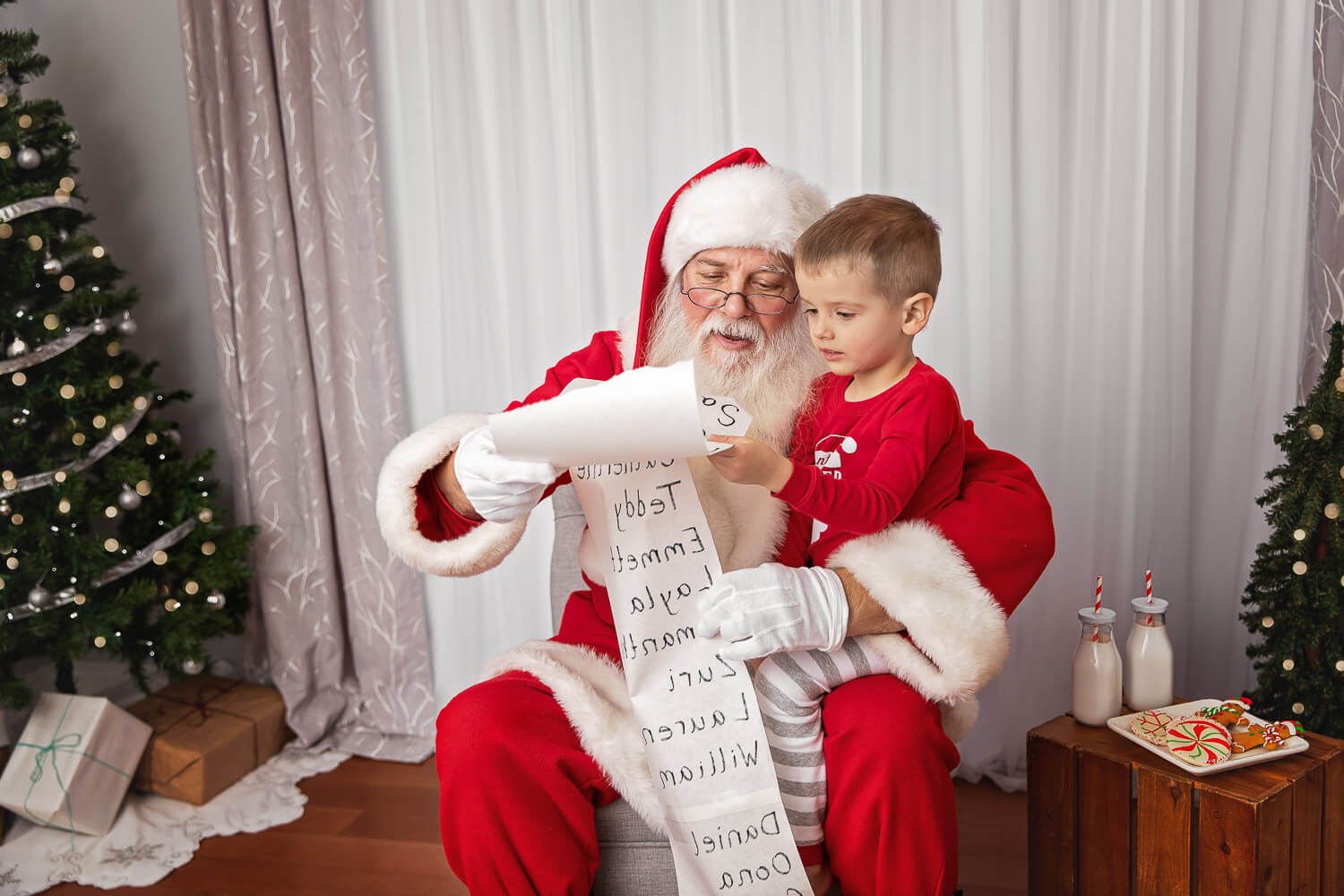 toddler boy sitting on Santa's lap looking at his