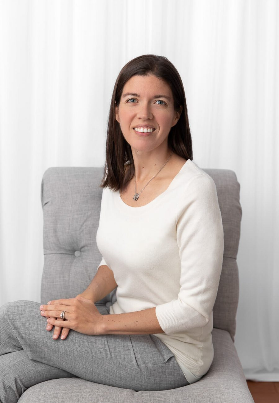 self portrait of Erin Massie sitting in a gray chair with white portraits behind