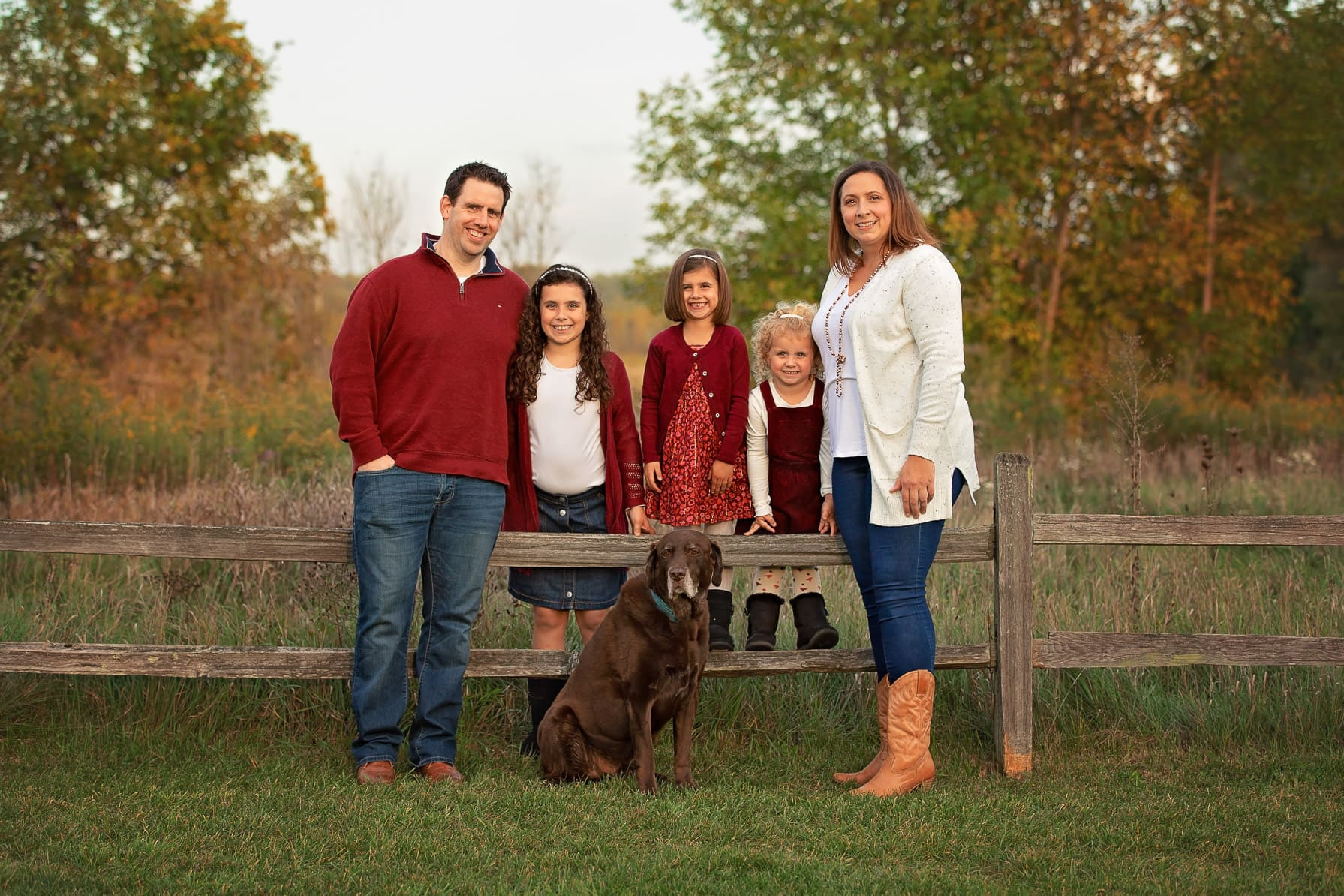 Family of 5 standing along a wooden fence with their dog during a Fall photo session at Roselle Park