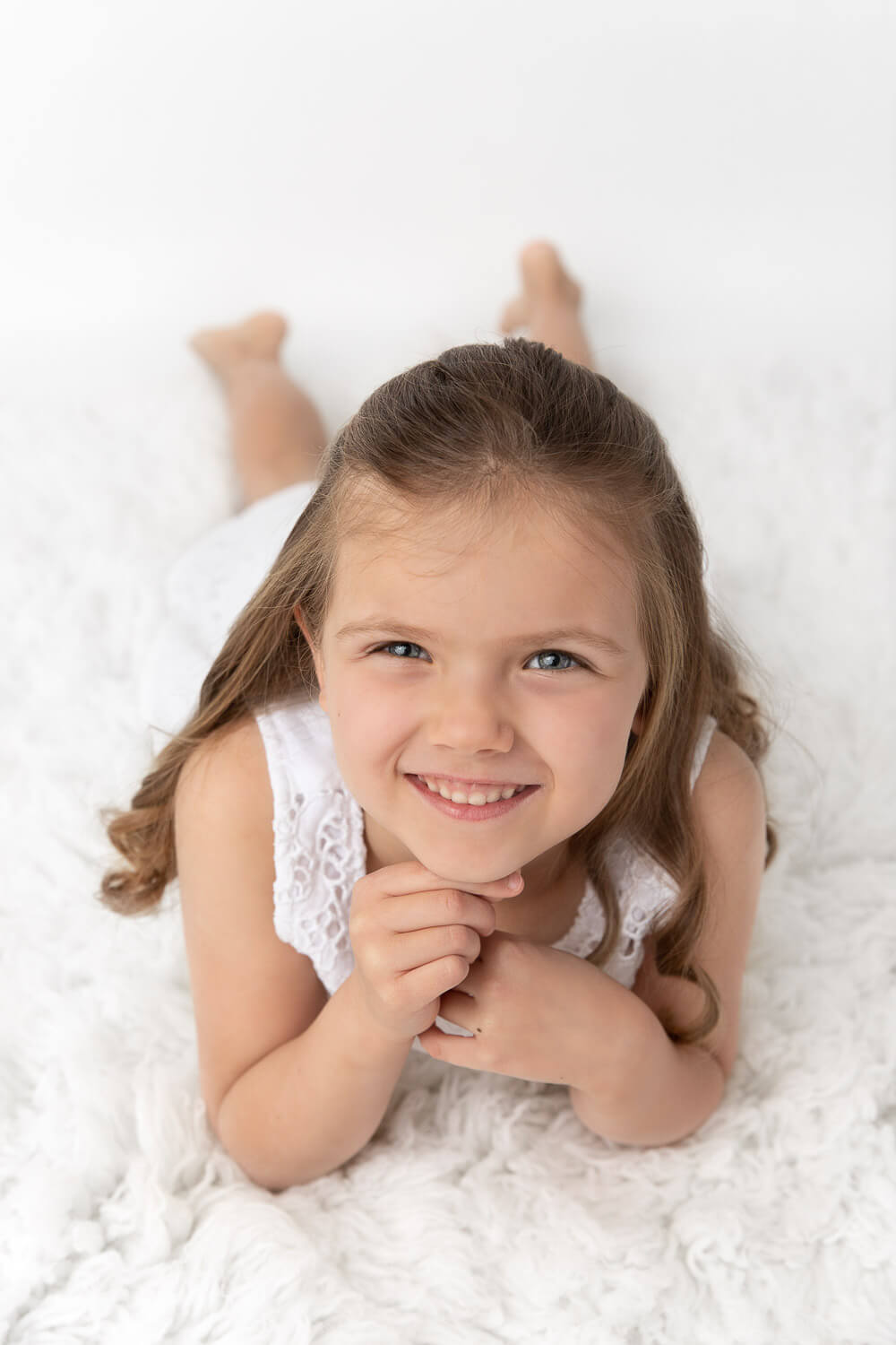 girl laying on white fur with hands under her chin smiling up at camera