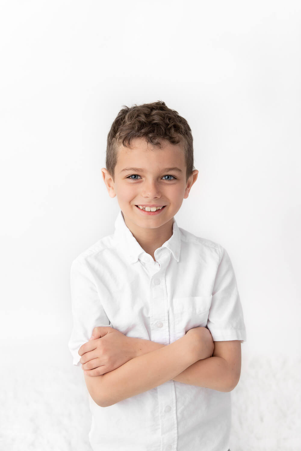 boy wearing white shirt with crossed arms smiling at camera in front of a white backdrop