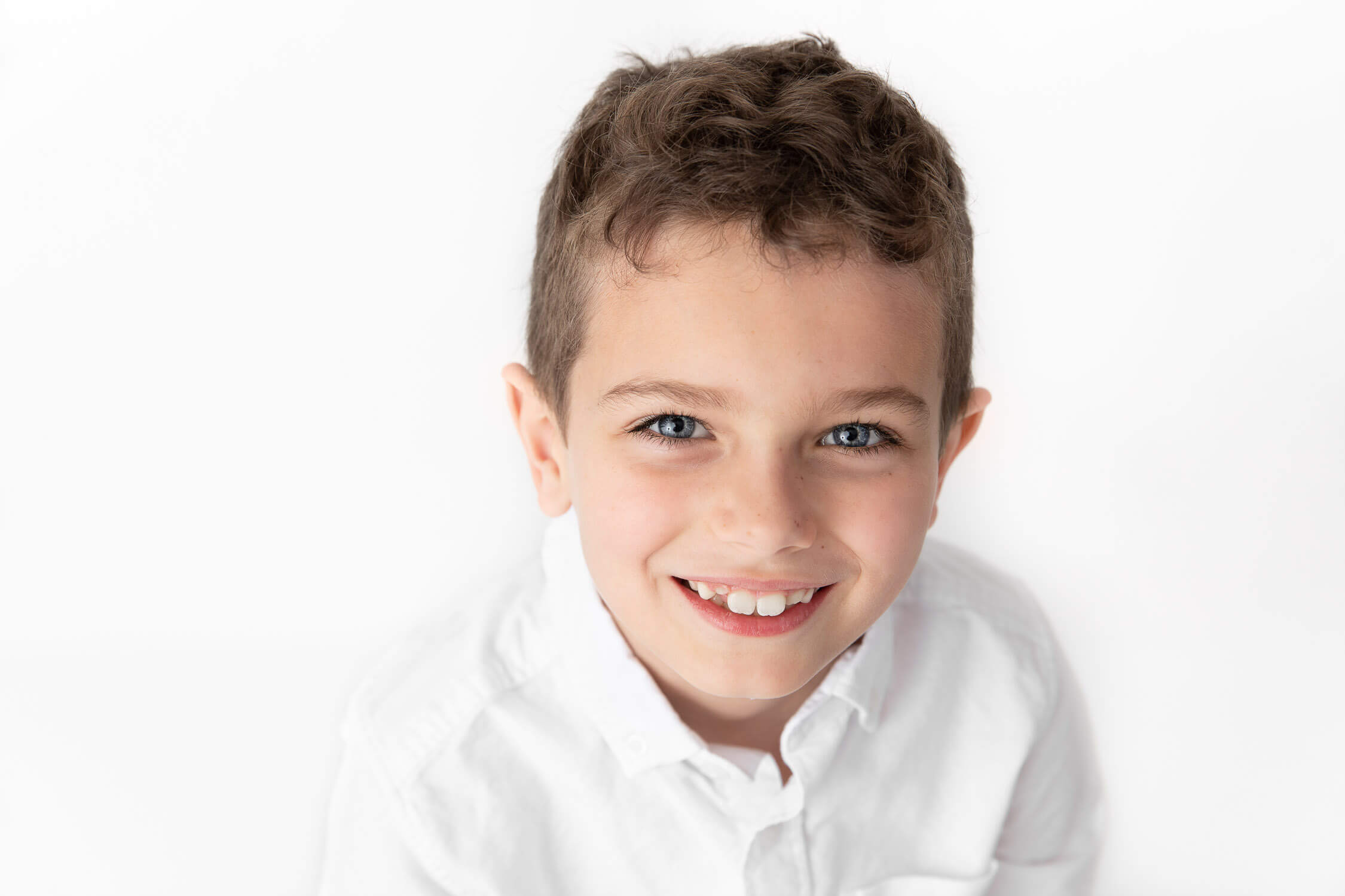 closeup of a boy wearing white shirt on a white background smiling at camera