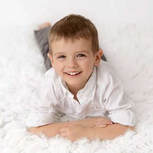 youngn boy wearing white button down shirt laying on stomach on white fur