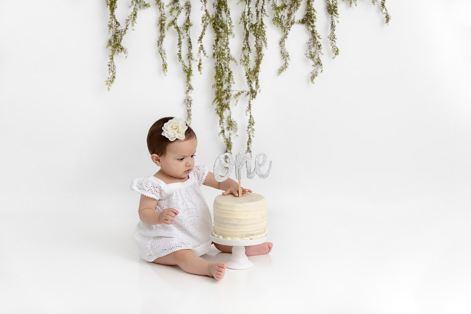 1 year old baby girl wearing a white dress sitting in a white room holding a birthday cake with a glitter ONE cake topper