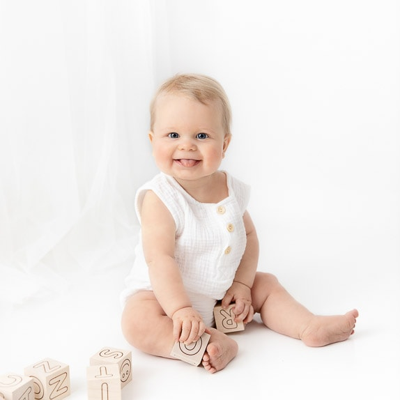 6 Month Baby Boy wearing white romper sitting on white room playing with natural wooden blocks