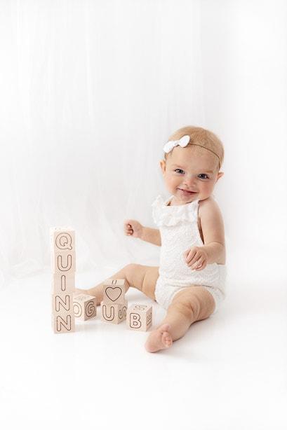 6 month baby girl sitting in White Studio stacking natural wood blocks
