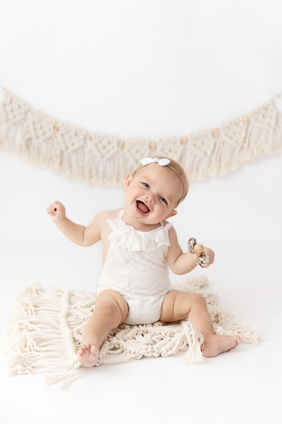 6 month old baby girl smiling and dancing for the camera while sitting on a macrame rug wearing a white romper