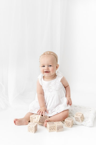 6 month baby girl sitting in a white studio wearing a white dress playing with neural wooden blocks