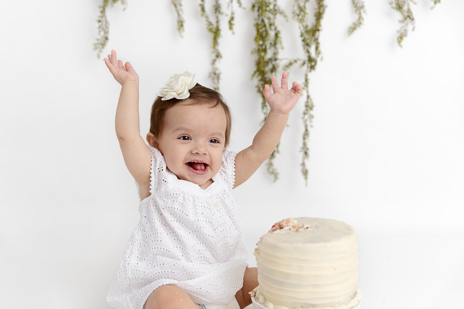 12 month old baby girl with a white birthday cake smiling big with her arms raised over her head