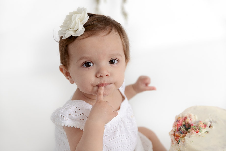 Close up of a 1 year old baby girl in a white studio eating a rainbow colored smash cake with her finger in her mouth
