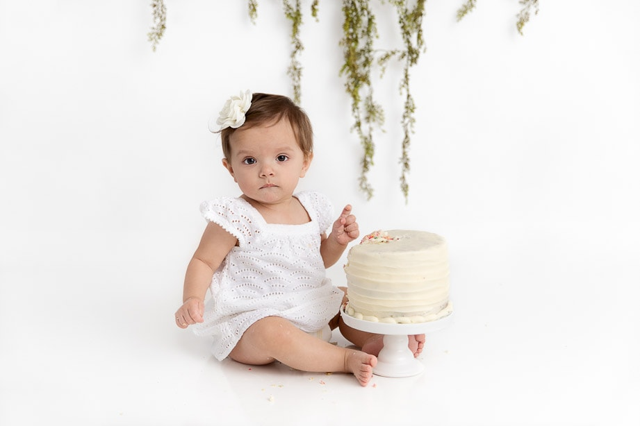 1 year old baby girl wearing a white dress staring at the camera with a big mash cake on a white stand
