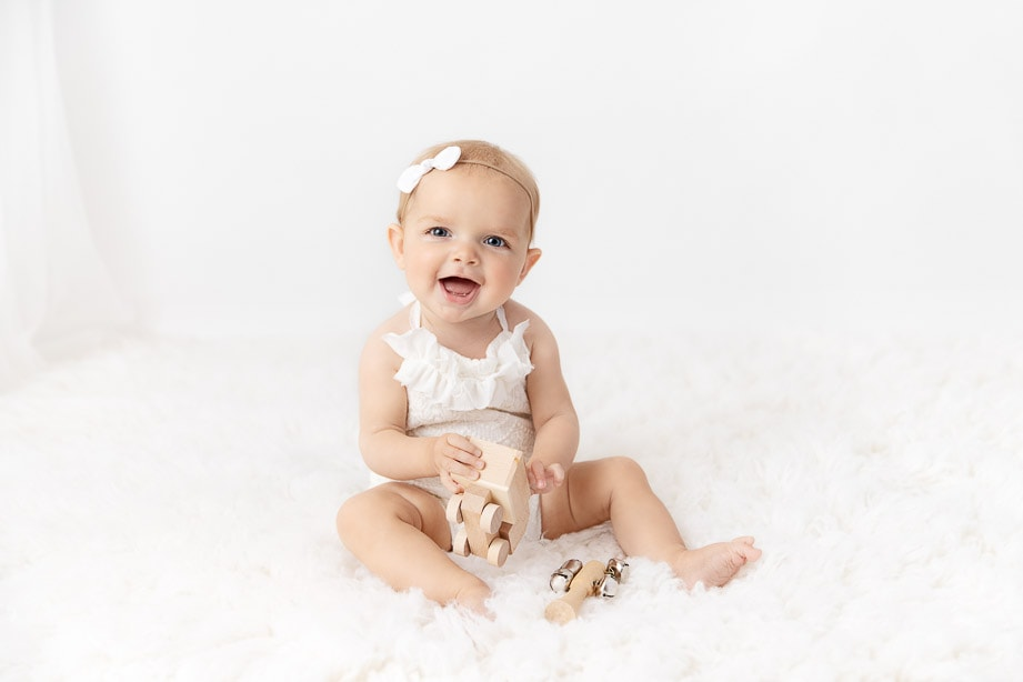 6 month baby girl sitting on a white fur playing with natural wooden toys