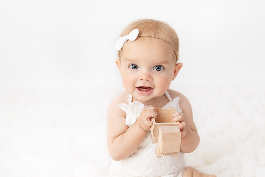 Close up of a 6 month baby girl wearing a white romper playing with a classic wooden truck on a white fur