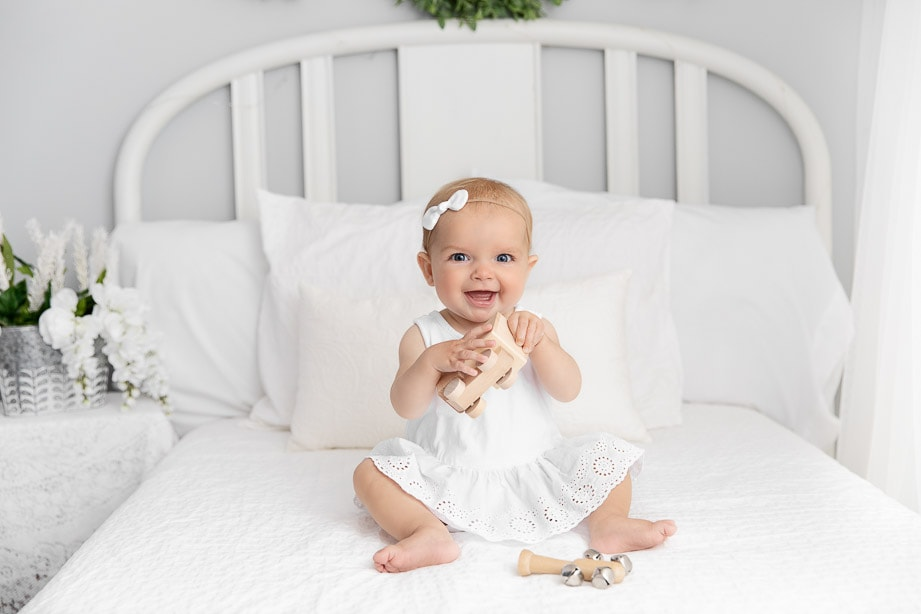 6 month baby girl wearing a white dress playing with classic toys on a white bed
