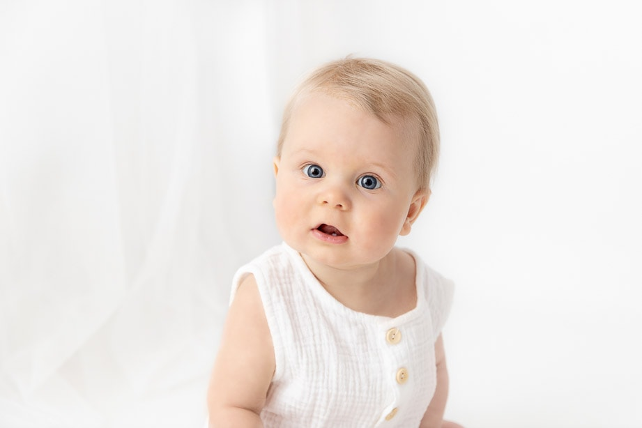 Close up of a 6 month baby boy with big blue eyes wearing a white romper near sheer white curtains