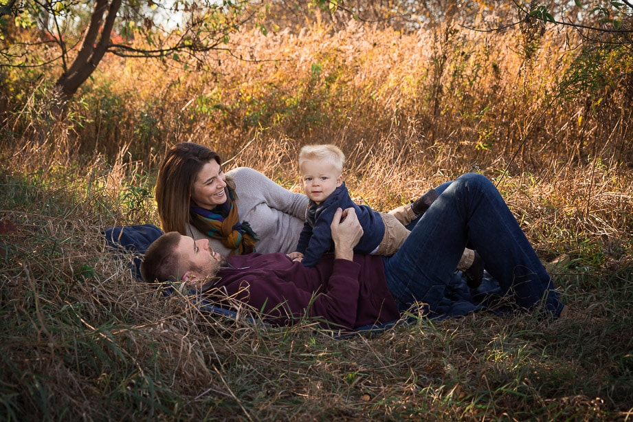 Mom and dad laying on a blanket in a tall grass field with baby boy on dad's stomach looking at camera