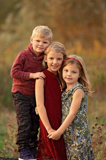 2 sisters and their brother standing together in a field during Fallr