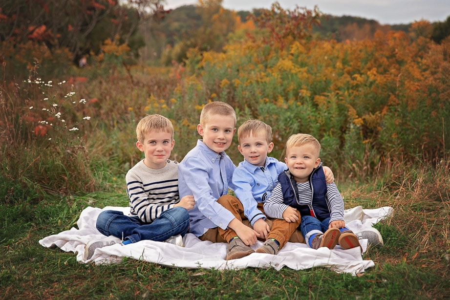 4 young brothers sitting together on a blanket in the middle of a colorful field in Fall