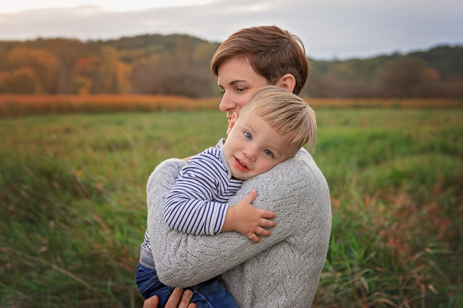 Baby boy leaning his head on mom's shoulder in a tall grass field at sunset in Roselle Park