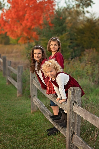 3 sisters standing along a wooden fence in front of a bright orange tree in Fall