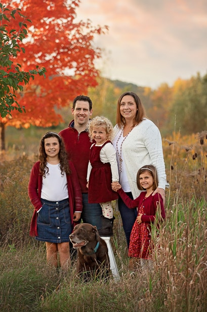 Family of 5 posed standing in tall grass with their dog in front of a bright orange tree