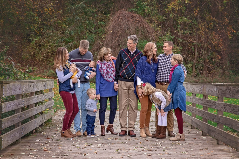 Extended family of 11 candidly interacting together while standing in the middle of a wooden bridge