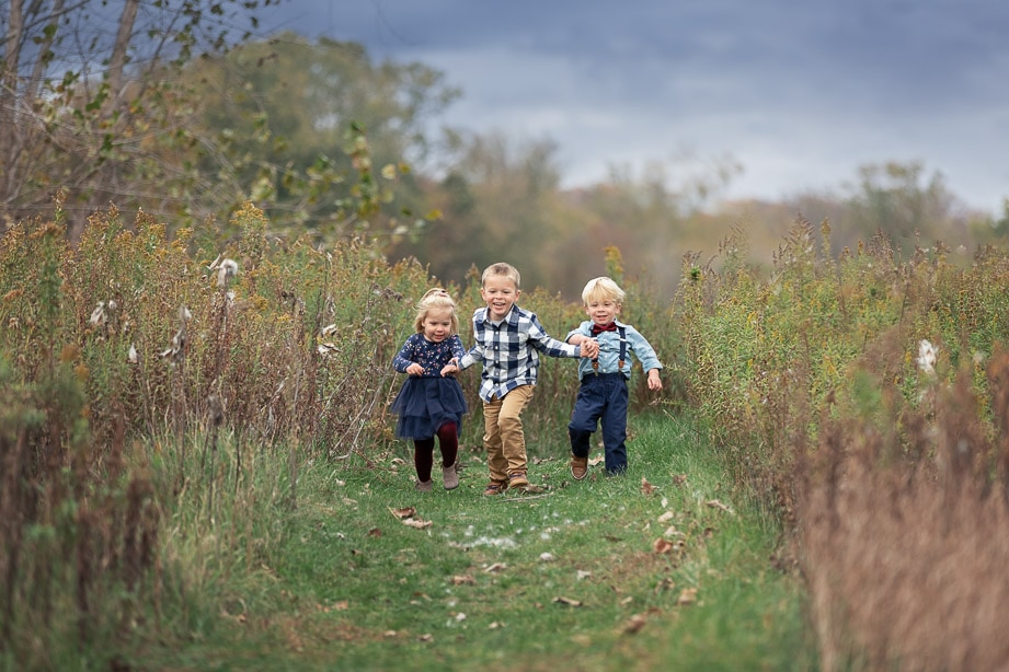 3 toddler siblings holding hands running through a path in tall grass