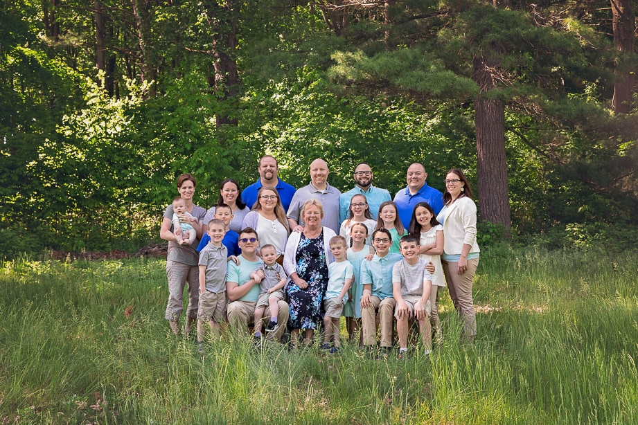 Large extended family of 21 posed together in a green grass field