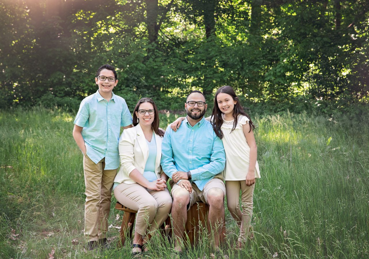 Family of 4 posed together in a green grass field with sunflare shining through green trees in the background