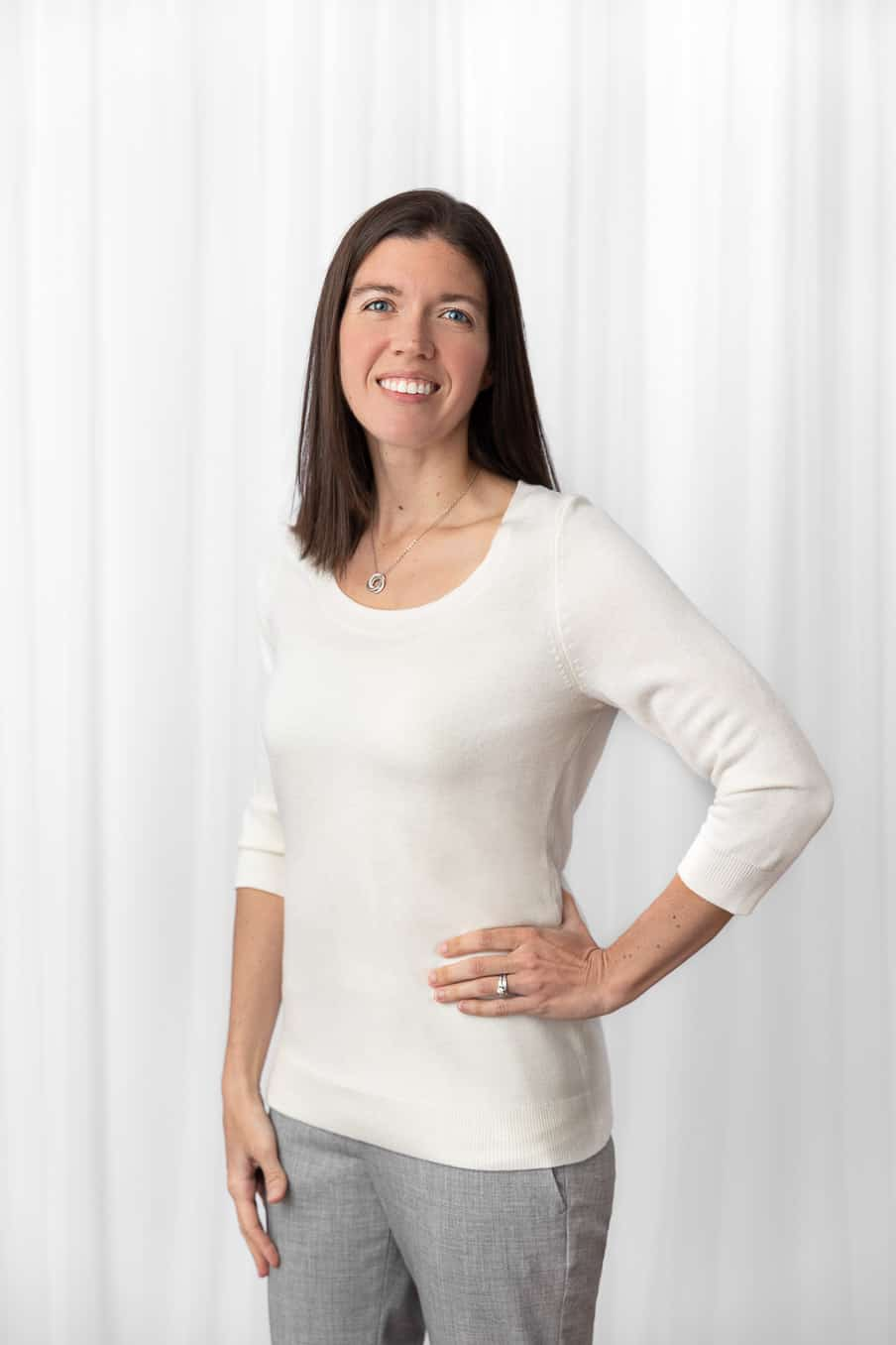 Portrait of Erin Massie standing in front of white sheer curtains in a white studio