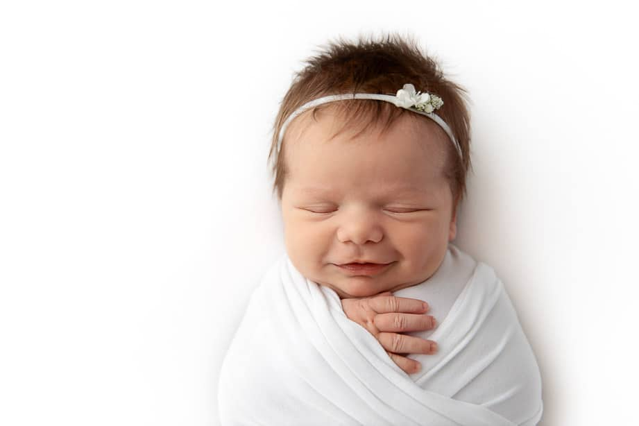 closeup of newborn girl smiling while sleeping wrapped in white fabric