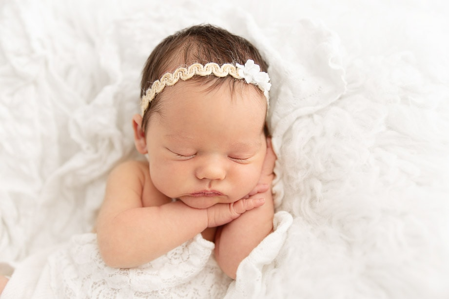 newborn baby girl laying on side with hands under cheek on white flokati