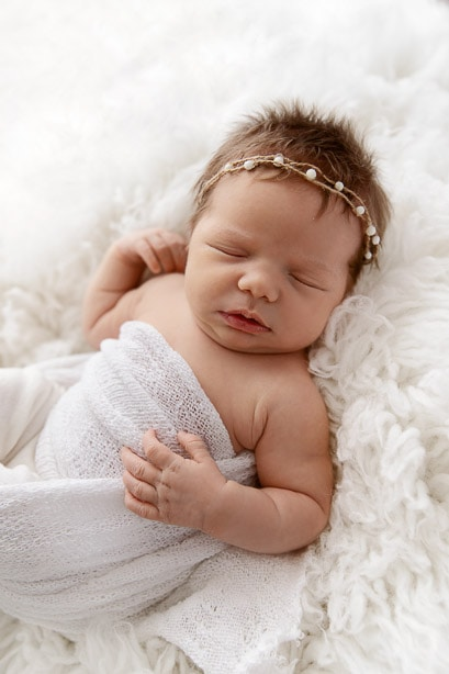 newborn baby girl wearing white bead headband sleeping on white fur