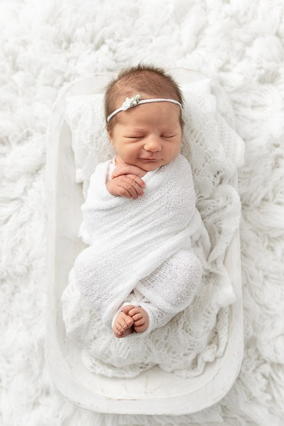newborn baby girl sleeping in a white wrap on a white dough bowl surrounded by white fur