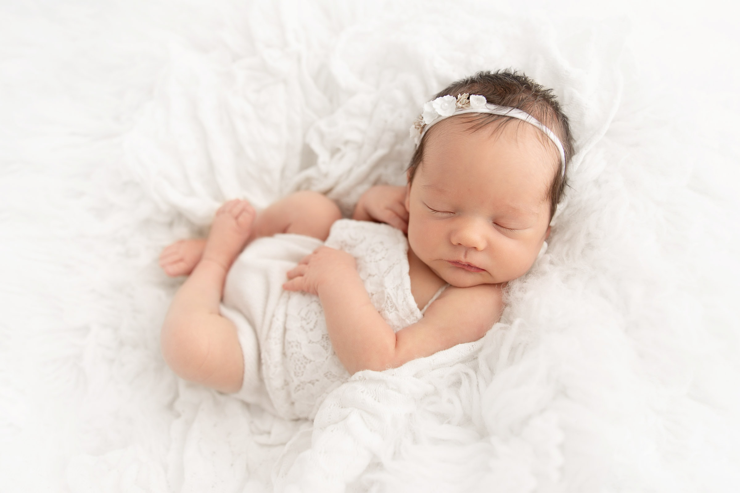Newborn girl wearing white romper laying on her back on white flokati