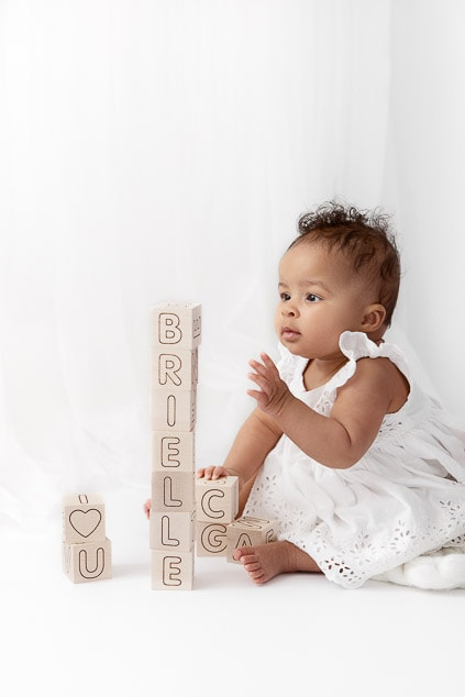Profile view of 6 month old girl sitting in front of a white sheer curtain reaching for a tower of wooden blocks