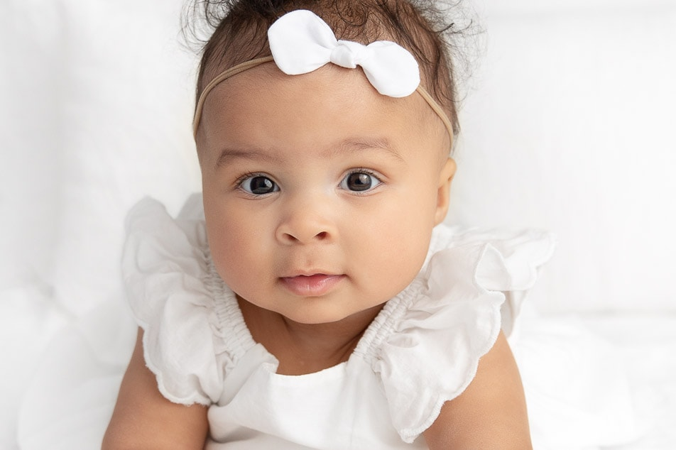 close up of a 6 month old baby girl leaning towards the camera wearing a white dress with white bow
