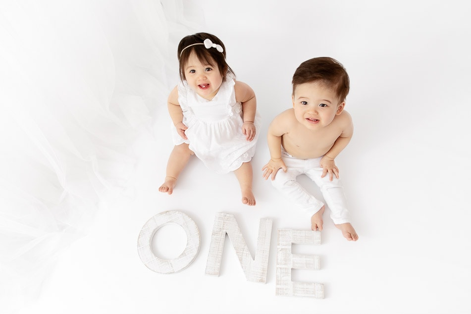 boy girl 1 year old twins sitting on the ground looking up at the camera with big wooden O-N-E letters