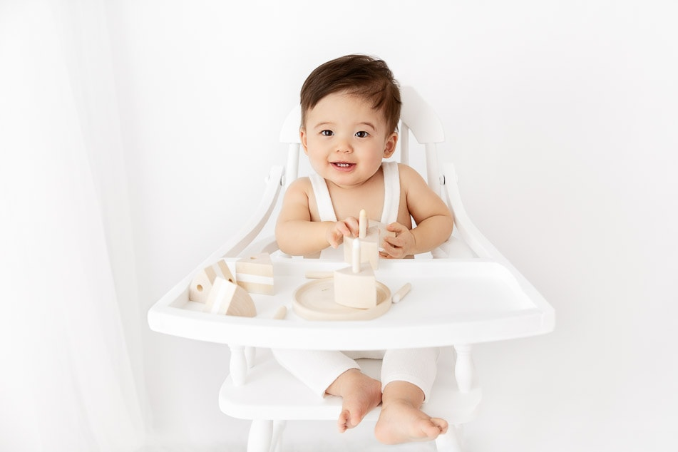 1 year old boy sitting in an antique white wood high chair with a wood birthday cake prop