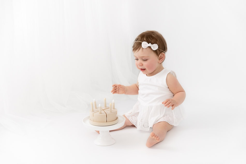 1 year old baby girl in front of a white sheer curtain with a wooden birthday cake prop